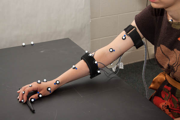 The small circles are part of the motion capture system that measure the motions. These marker based systems will be replaced with inertial measurement systems in the wearable usage. The band on the forearm are the surface electromyography sensors. Photo courtesy of Leia Stirling.